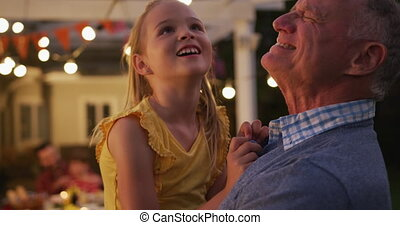 Grandfather playing with his granddaughter outdoors - ...