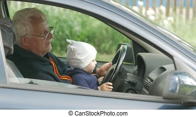 Grandfather plays with the boy in the car while driving. The...