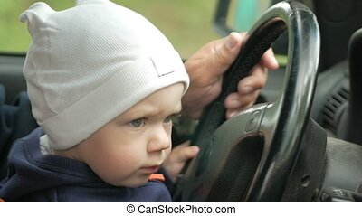 Grandfather plays with the boy in the car while driving. The grandson is very happy and twists the different buttons