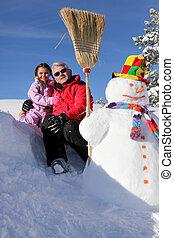 grandfather posing with granddaughter at ski resort
