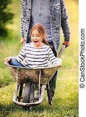 Grandfather pushing his grandaughter in a wheelbarrow. -...