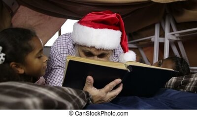 Grandfather reading a book to his granddaughters