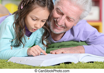 grandfather reading book with  grandaughter