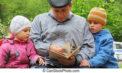 grandfather reads to boys and girls the book in park on a bench