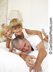 Grandfather Relaxing On Bed With Grandchildren