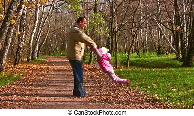 grandfather rotate child in autumn park