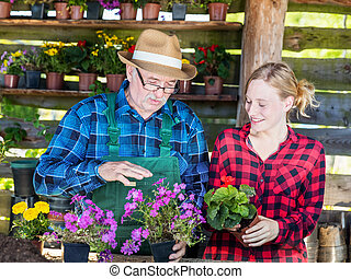 Grandfather showing grandaughter how to plant flowers. -...