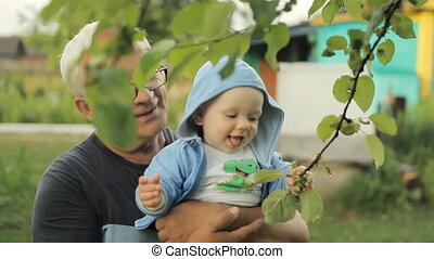 Grandfather showing grandson apple tree. Beautiful baby smiling and touching plant