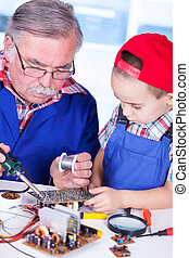 Grandfather showing PCB soldering to grandchild (Shallow...