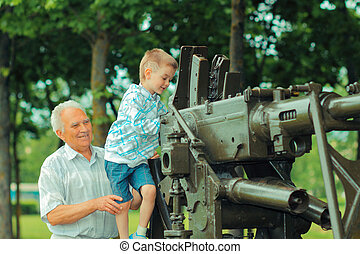 Grandfather shows for his grandson old military artillery...