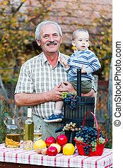 Grandfather smiling - Happy grandpa holding his sucessor in ...