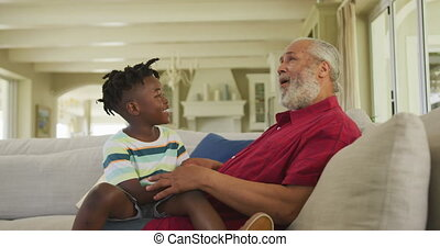 Grandfather talking to his grandson at home - Senior African...