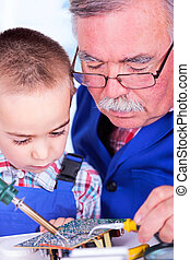 Grandfather teaching grandchild soldering with iron -...