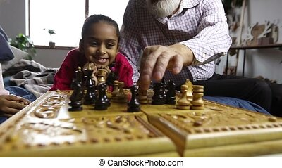 Grandfather teaching grandchildren chess at home -...