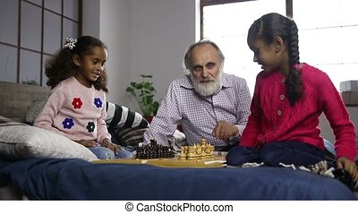 Grandfather teaching grandchildren chess at home - Handsome...