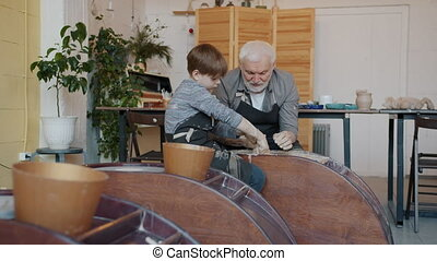 Grandfather is teaching little boy in pottery class using throwing-wheel working with clay in modern arts studio. Family hobby and occupation concept.