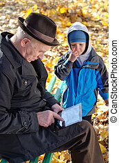 Grandfather using a tablet watched by his grandson