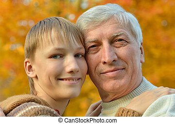 Grandfather with boy in autumn park