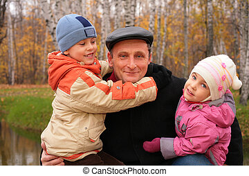 Grandfather with children in autumnal park