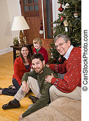 Grandfather with family sitting by Christmas tree