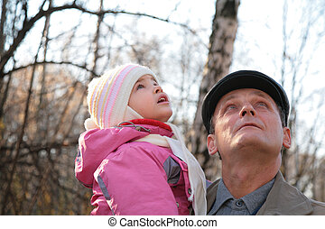 Grandfather with  granddaughter on hands outdoor look upward