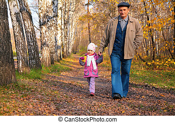 Grandfather with granddaughter walk in park in autumn