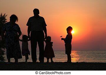 Grandfather with grandmother and the children against the background of sunset