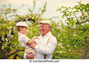 grandfather with grandson having fun in spring garden