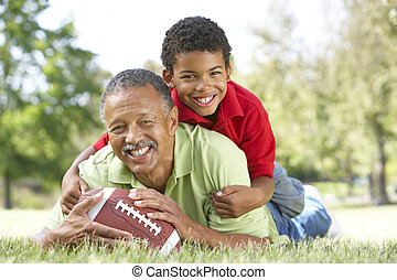 Grandfather With Grandson In Park With American Football