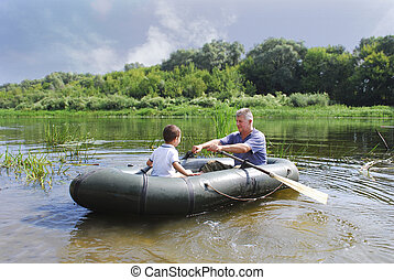 Grandfather with grandson swim in a rubber boat on the river.