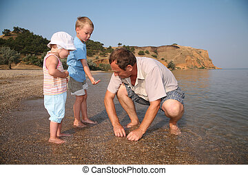 Grandfather with grandsons on beach