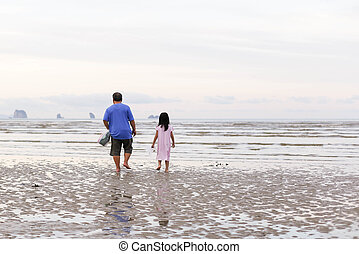 Grandfather with his granddaughter walking on a beach early...