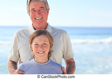 Grandfather with his grandson on the beach