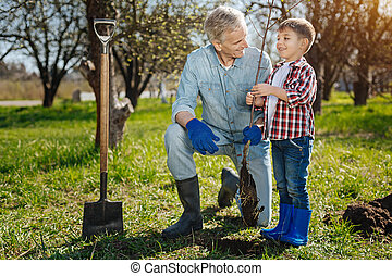 Grandfather with his grandson working in garden