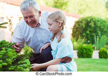 Grandfather with his little blonde grandchild having fun together
