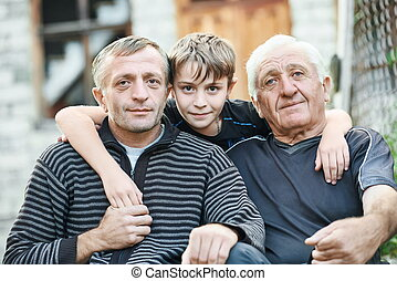 Grandfather with his son and grandson near country house