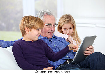 Grandfather with kids using electronic tab