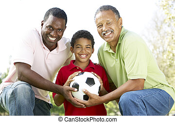 Grandfather With Son And Grandson In Park With Football