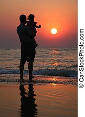 Grandfather with the child against the background of sunset at sea in water