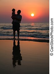 Grandfather with the child against the background of sunset at sea