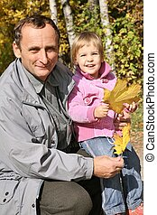 grandfather with the granddaughter in the park in autumn 2