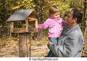 grandfather with the granddaughter in the park in autumn