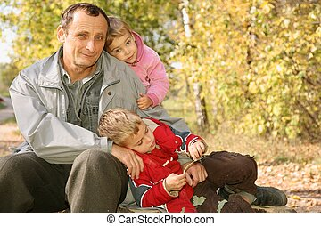 grandfather with the grandson and the granddaughter in the park in autumn
