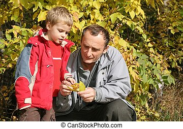 grandfather with the grandson in the park in autumn