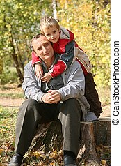 grandfather with the grandson sit in park  in autumn