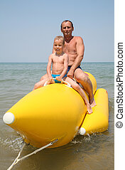 grandfather with the grandson they sit on the inflatable boat