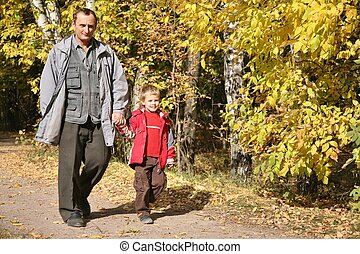 grandfather with the grandson walk in park  in autumn