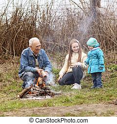 Grandfather with two grandchildren sitting around the campfire