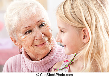 A closeup of a grandma and a granddaughter looking at each other