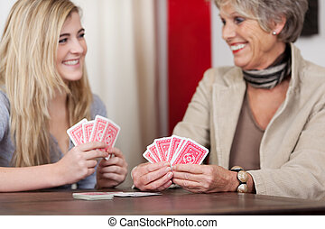 Grandma And Granddaughter Playing Cards - Cheerful...